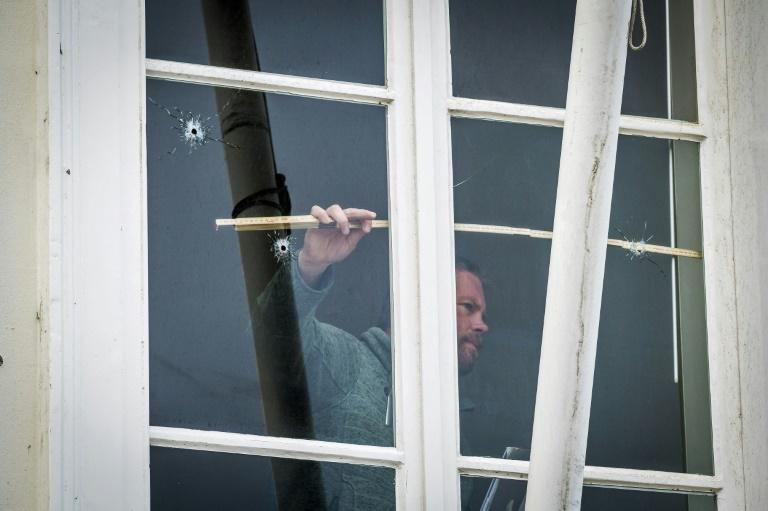 A technician takes measures of a window with bullet holes at the Embassy of Saudi Arabia in The Hague, after it has been shot at on November 12, 2020