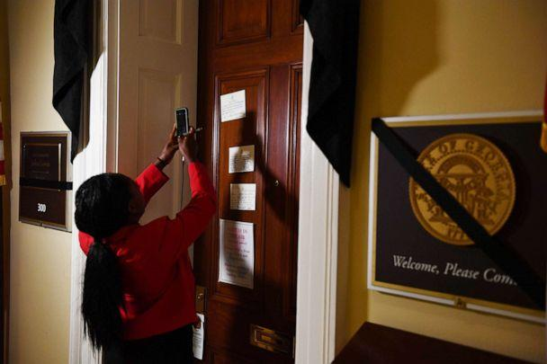 PHOTO: A woman takes a photo with her cellphone of notes left at the office door of Rep. John Lewis who died July 18, 2020, at age 80, at the U.S. Capitol on July 20, 2020, in Washington. (Brendan Smialowski/AFP via Getty Images)