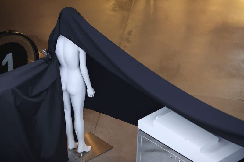 A mannequin is used to hang a piece of fabric on a closed business at a mall following the implementation of stricter social-distancing and self-isolation rules to limit the spread of the coronavirus disease (COVID-19) in Sydney