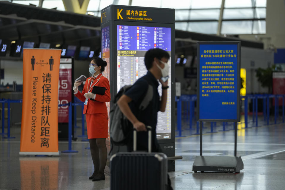 A passenger wearing a face mask to help curb the spread of the coronavirus pushes his luggage past a masked airliner staff stand near quiet check-in counters at Pudong International Airport in Shanghai, China, Sunday, July 25, 2021. Airline flights were canceled in eastern China and cargo ships were ordered out of the area Saturday as Typhoon In-fa churned toward the mainland after dumping rain on Taiwan. (AP Photo/Andy Wong)