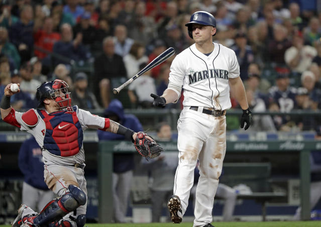 Seattle Mariners' Kyle Seager flips his bat after striking out swinging as Boston Red Sox catcher Christian Vazquez returns the ball to the pitcher during the seventh inning of a baseball game Thursday, June 14, 2018, in Seattle. (AP Photo/Elaine Thompson)