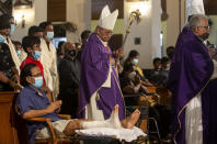 Cardinal Malcolm Ranjith, archbishop of Colombo, center, looks at a survivor of 2019 Easter Sunday attacks as he arrives to conduct a service at St. Anthony's Church in Colombo, Sri Lanka, Wednesday, April 21, 2021. Wednesday marked the second anniversary of the serial blasts that killed 269 people. (AP Photo/Eranga Jayawardena)