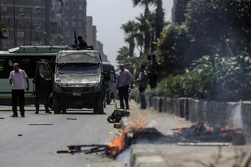 Egyptian policemen stand guard in the middle of al-Haram street in Cairo on August 14, 2014, during clashes with Muslim Brotherhood supporters following a rally marking the first anniversary of a brutal Cairo crackdown (AFP Photo/Mohamed El-Shahed)