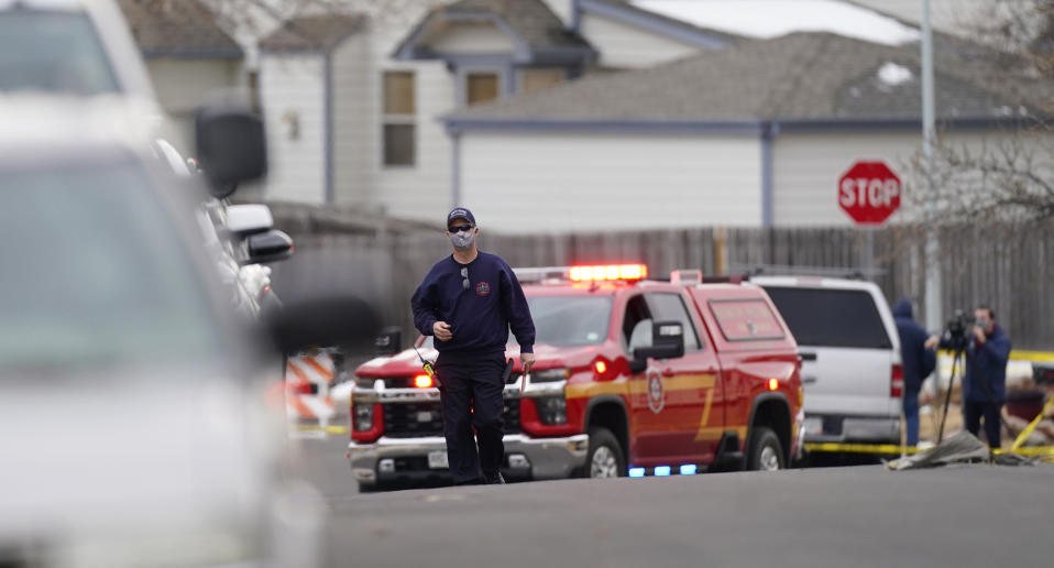 A North Metro Fire Department investigator heads up Elmwood Street to view damage from debris that fell from a commercial passenger plane in Broomfield, Colo., as the plane shed parts while making an emergency landing at nearby Denver International Airport Saturday, Feb. 20, 2021. (AP Photo/David Zalubowski)