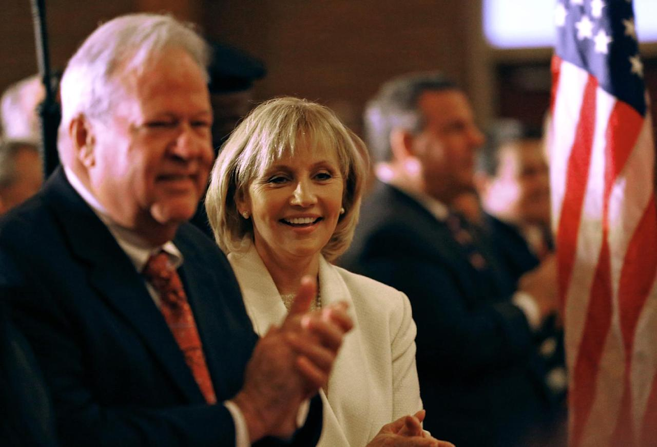 New Jersey Lt. Gov. Kim Guadagno with her husband Michael during a prayer service in celebration of her inauguration with Gov. Chris Christie at the New Hope Baptist Church on Tuesday, Jan. 21, 2014 in Newark. The celebrations to mark the start of Christie's second term could be tempered by investigations into traffic tie-ups that appear to have been ordered by his staff for political retribution and an allegation that his administration linked Superstorm Sandy aid to approval for a real estate project. (AP Photo/Rich Schultz)