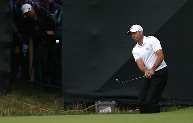 Spectators peak through a gap to watch Sergio Garcia of Spain chipping onto the 15th green during the third day of the British Open Golf championship at the Royal Liverpool golf club, Hoylake, England, Saturday July 19, 2014. (AP Photo/Scott Heppell)