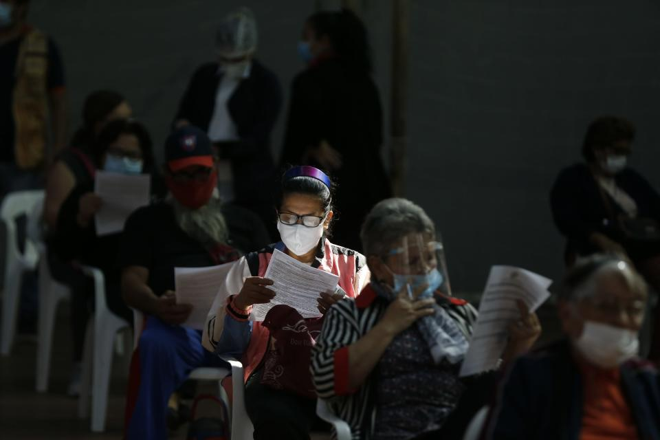 People over age 65 read instructions before getting a shot of the AstraZeneca COVID-19 vaccine in San Lorenzo, Paraguay, Tuesday, May 18, 2021. (AP Photo/Jorge Saenz)