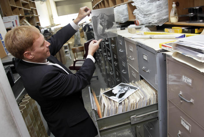"""In this Wednesday, July 25, 2012 photo, Stuart Scheinman, a partner in Las Vegas-based Premier Collectibles., looks at an original negative of actress Bette Davis in the files of Movie Star News in New York. Movie Star News, a New York institution since 1939 credited with creating the concept of pin-up art, has been shuttered, and with it nearly 3-million Hollywood-related posters, vintage photographs and original negatives are destined for a different future. Last week, the Manhattan store announced it had sold its entire inventory, including 1,500 original bondage images of the """"Queen of Pin-Ups"""" Bettie Page, to two partners of a Las Vegas collectibles company for an undisclosed sum. (AP Photo/Richard Drew)"""