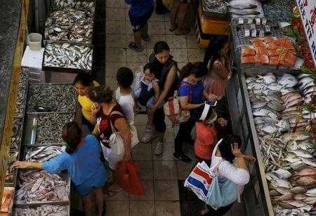 People shop for fish at a wet market in Singapore
