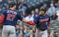 Minnesota Twins' Jorge Polanco is congratulated by Ryan Jeffers after scoring a run on a groundout by Alex Kirilloff during the third inning of a baseball game against the Seattle Mariners, Wednesday, June 16, 2021, in Seattle. (AP Photo/Stephen Brashear)