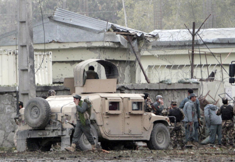 Afghan army and police surround the area after a multi-pronged attack on a police station in Jalalabad, the capital of eastern Nangarhar province, Afghanistan, Thursday, March 20, 2014. Taliban insurgents staged the attack, using a suicide bomber and gunmen to lay siege to the station, government officials said. Two remotely detonated bombs also exploded nearby. (AP Photo/Rahmat Gul)