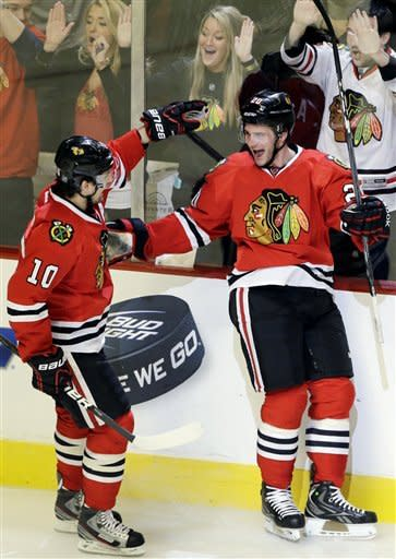 Chicago Blackhawks' Brandon Saad, right, celebrates with Patrick Sharp after scoring his goal during the third period of an NHL hockey game against the San Jose Sharks in Chicago, Friday, Feb. 22, 2013. The Blackhawks won 2-1. The Blackhawks set an NHL record by recording a point in their 17th consecutive game to start a season. (AP Photo/Nam Y. Huh)