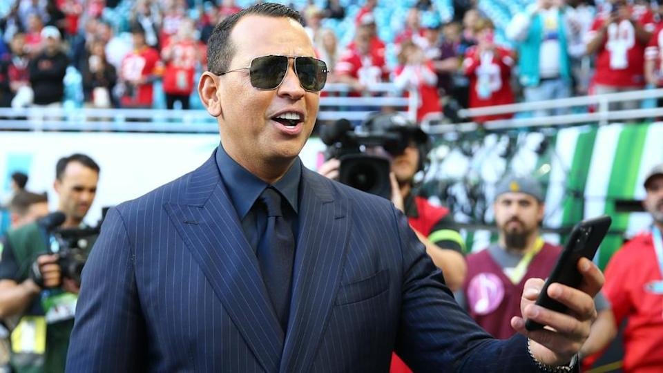 Alex Rodriguez smiling with phone in hand