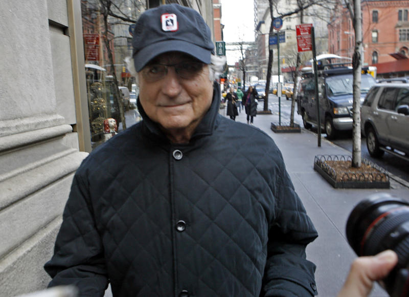 FILE - In this Dec. 17, 2008 file photo, Bernard Madoff returns to his Manhattan apartment after making a court appearance in New York.  In December 2008, two of Bernard Madoff's most loyal employees met on a Manhattan street corner and fretted over a closely held secret that the rest of the world would learn about eight days later: that their boss, Madoff,  was a con man for the ages.  The exchange was recounted for the first time in a newly rewritten indictment this week expanding the case and charges against five defendants headed for a trial next year. The indictment brings into sharper focus the final few years of a fraud the government says dated to at least the early 1970s, two decades before Madoff claimed it began and well before 1992, when the government said in its original case against the defendants that the conspiracy began. (AP Photo/Jason DeCrow, File)