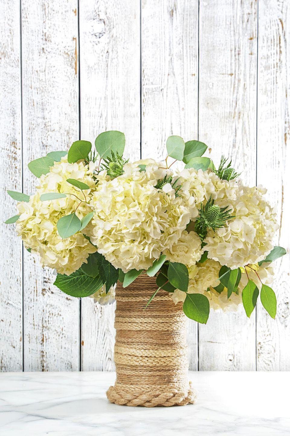 <p>Jute rope turns a cheap vase into a statement piece. It's as easy as it looks: Simply, hot-glue jute rope around a vessel for a beach-ready look. </p>