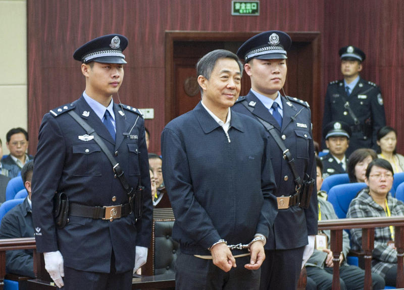 In this photo released by China's Xinhua News Agency, ousted Chinese politician Bo Xilai, center, stands as the Shandong Provincial Higher People's Court announces the decision of the second trial of Bo, in Jinan, China's Shandong Province. The court on Friday upheld Bo's conviction and life sentence for corruption and abuse of power in the final decision of one of China's most politically charged trials in decades. (AP Photo/Xinhua, Xie Huanchi) NO SALES