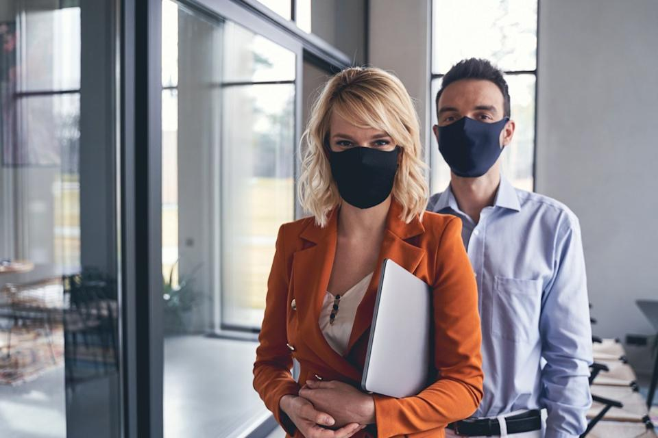 Front view of business people wearing protective masks in the office during the quarantine period