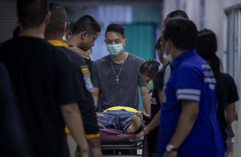 Family members visit their relative, a victim of the mass shooting, at a morgue, in Korat, Nakhon Ratchasima, Thailand, Sunday, Feb. 9, 2020. Thai officials say a soldier who went on a shooting rampage and killed numerous people and injured dozens of others has been shot dead inside the mall in northeastern Thailand. (AP Photo/Gemunu Amarasinghe)