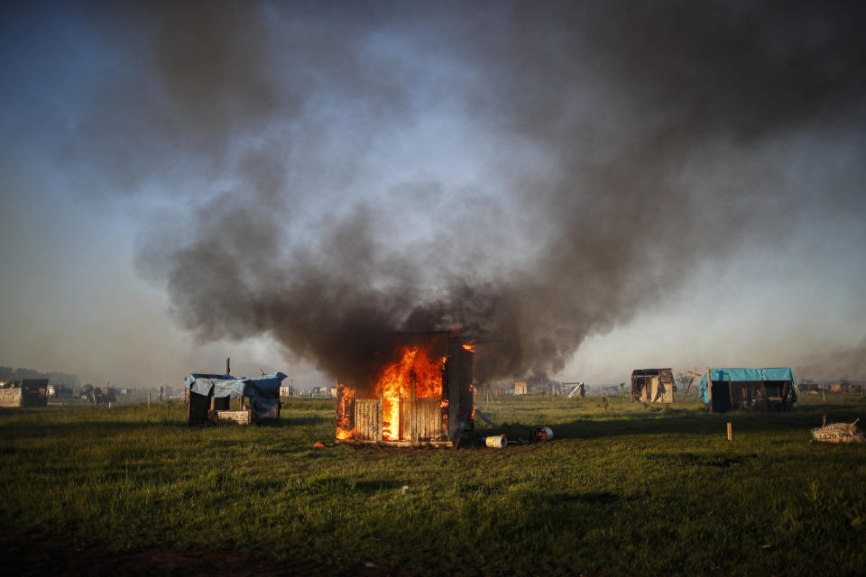 A shack home burns as people are evicted from a squatters camp by police in Guernica, Buenos Aires province, Argentina, Thursday, Oct. 29, 2020. A court ordered the eviction of families who have been squatting at the camp since July, but the families say they have nowhere to go amid the COVID-19 pandemic. (AP Photo/Natacha Pisarenko)