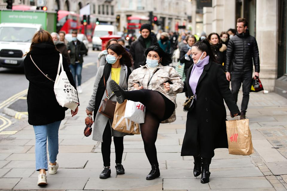 A shopper wearing a face mask strikes a pose on Regent Street in London, England, on December 4, 2020. London has returned to so-called Tier 2 or 'high alert' coronavirus restrictions since the end of the four-week, England-wide lockdown on Wednesday, meaning a reopening of non-essential shops and hospitality businesses as the festive season gets underway. Rules under all three of England's tiers have been strengthened from before the November lockdown, however, with pubs and restaurants most severely impacted. In London's West End, Oxford Street and Regent Street were both busy with Christmas shoppers this afternoon, meanwhile, with the retail sector hoping for a strong end to one of its most difficult years. (Photo by David Cliff/NurPhoto via Getty Images)