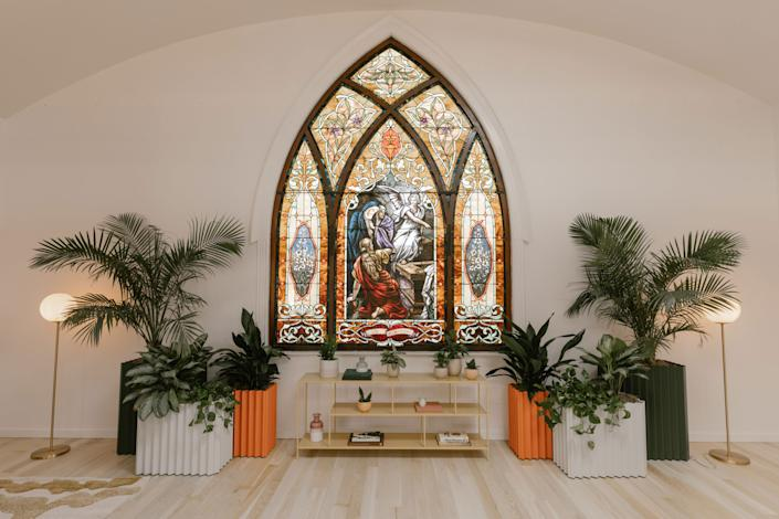"<div class=""caption""> The impressive stained glass in the Worship Hall is definitely a statement. We love the juxtaposition of modern pieces like the <a href=""https://mostmodest.com/collections/planters-furniture/products/tess-planter"" rel=""nofollow noopener"" target=""_blank"" data-ylk=""slk:colorful aluminum planters"" class=""link rapid-noclick-resp"">colorful aluminum planters</a> by Most Modest. </div>"