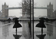 FILE - In this Thursday, Jan. 14, 2021 file photo, a woman is reflected in a window as she braves the wind and rain while walking towards Tower Bridge in London, during England's third national lockdown to curb the spread of coronavirus. Thanks to an efficient vaccine roll out program and high uptake rates, Britain is finally saying goodbye to months of tough lockdown restrictions. From Monday May 17, 2021, all restaurants and bars can fully reopen, as can hotels, cinemas, theatres and museums, and for the first time since March 2020, Britons can hug friends and family and meet up inside other people's houses. (AP Photo/Kirsty Wigglesworth, File)