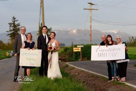 The family of Liz and Matt Peters celebrate their wedding with homemade signs on the border of Canada and the U.S.