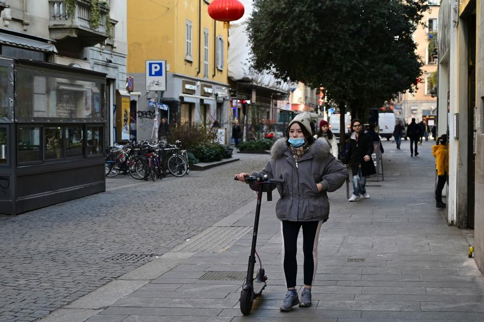 """A woman wearing a mask walks by her electric scooter in via Paolo Sarpi, the commercial street of the chinese district of Milan on January 30, 2020. - Several well-known figures in the Chinese community in Italy on January 30, 2020 denounced """"Discrimination without distinction"""" and """"latent racism"""" from Italians frightened by the coronavirus epidemic and the risks of contagion. (Photo by Miguel MEDINA / AFP) (Photo by MIGUEL MEDINA/AFP via Getty Images)"""