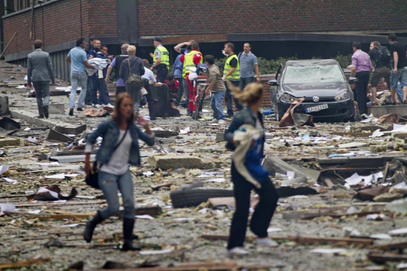 NORWAY OUT Two women walk over debris while rescue workers in the background interact with people near an explosion site in Oslo after two bombs rocked the Norwegian capital on July 22, 2011. Militants staged twin bomb and shooting attacks in Norway Friday, leaving at least 11 dead as a blast tore through government buildings and a gunman opened fire at a youth meeting of the ruling party. Many were also reported wounded from the bomb blast in central Oslo and the shooting at a summer school meeting of Prime Minister Jens Stoltenberg's ruling Labour Party outside the capital. AFP PHOTO / SCANPIX / THOMAS WINJE OIJORD (Photo credit should read THOMAS WINJE OIJORD/AFP/Getty Images)