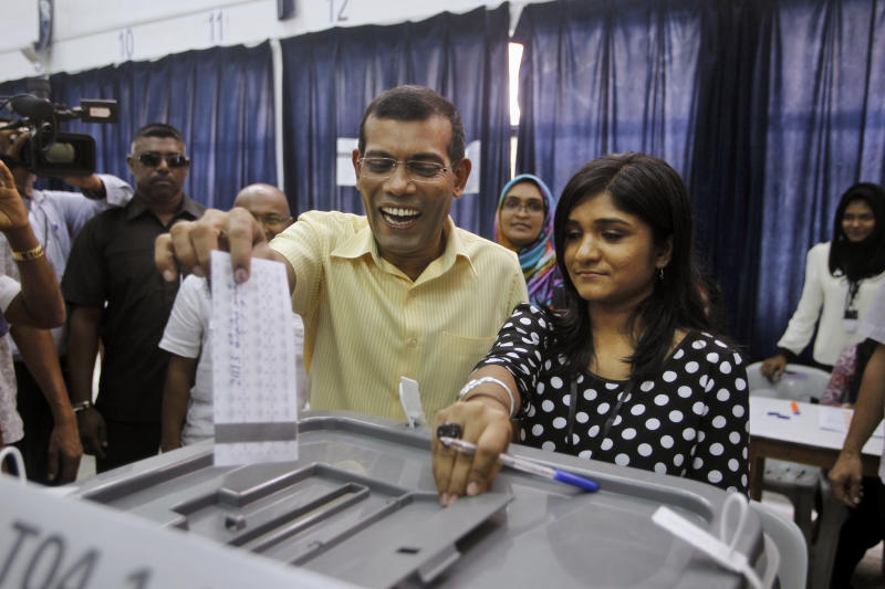 Maldives' former President and candidate in the presidential elections Mohamed Nasheed, center left, casts his vote in Male, Maldives, Saturday, Nov. 9, 2013. After two months of political bickering and repeated failure to hold an election, Maldives voters headed to the polls Saturday to elect a new president for their vulnerable new democracy. (AP Photo/Sinan Hussain)