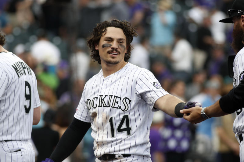 Colorado Rockies' Tony Wolters is congratulated after hitting a sacrifice fly to bring in the winning run off Baltimore Orioles relief pitcher Mychal Givens in the ninth inning of a baseball game Sunday, May 26, 2019, in Denver. (AP Photo/David Zalubowski)