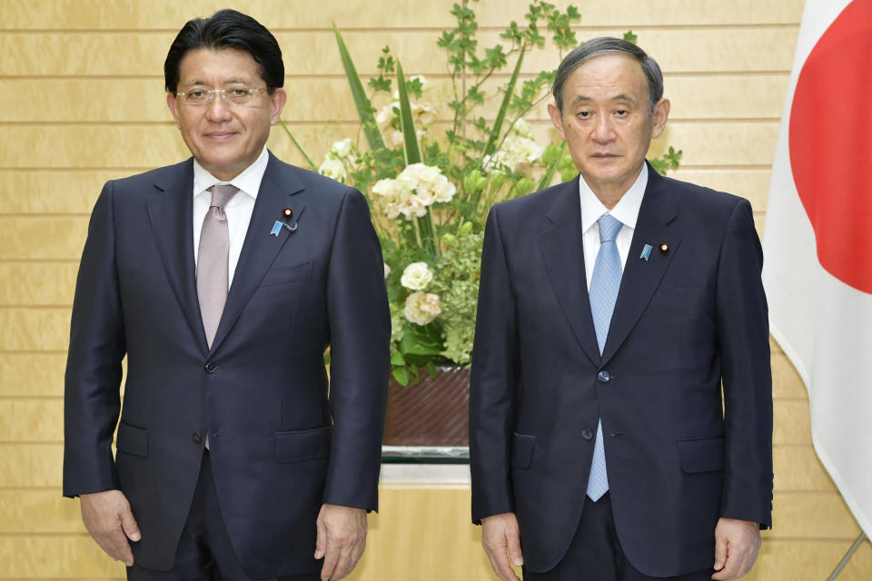 Japan's Prime Minister Yosihide Suga, right, poses with Digital Transformation Minister Takuya Hirai following a launch of launch of a new Digital Agency, at Suga's official residence in Tokyo Wednesday, Sept. 1, 2021. Japan was looking to give its government services and record keeping a technological upgrade with Wednesday's launch of the agency, hoping to bring a much needed overhaul to antiquated systems that have had their shortfalls highlighted by the pandemic. (Kyodo News via AP)
