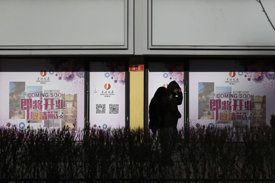 People walk by vacant retail shop lots in Beijing, Tuesday, Jan. 15, 2019. China plans to slash taxes, step up spending and provide ample financing to private and small enterprises to help counter the country's worst slowdown since the global financial crisis and the impact of a bruising trade war with the U.S. (AP Photo/Andy Wong)
