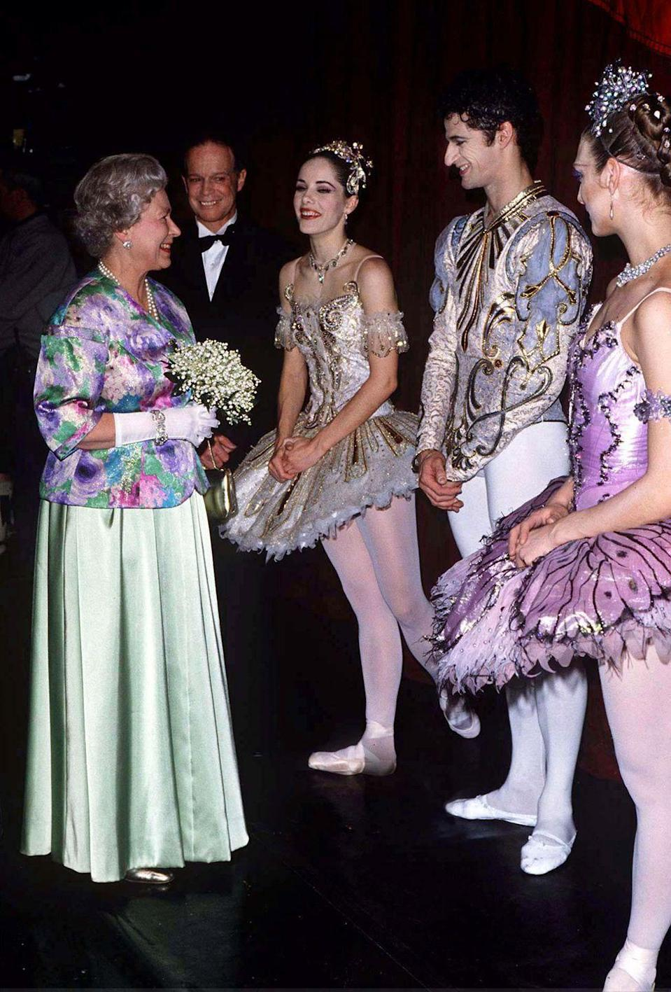 """<p>The Queen visits with dancers from """"Sleeping Beauty"""" at the Royal Opera House in 1996.</p>"""