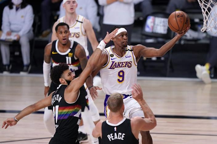 Los Angeles Lakers guard Rajon Rondo (9) takes a shot as Denver Nuggets' Jamal Murray, left, and Mason Plumlee, bottom, defend during the first half of Game 3 of the NBA basketball Western Conference final Tuesday, Sept. 22, 2020, in Lake Buena Vista, Fla. (AP Photo/Mark J. Terrill)