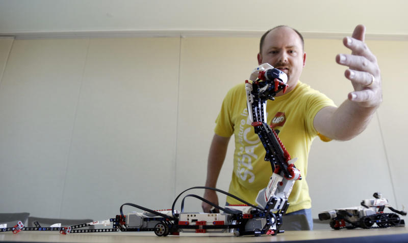 In this Aug. 13, 2013, photo, Will Gorman plays with a robotic Lego Mindstorms unit shaped like a snake in Redwood City, Calif. Lego's new Mindstorms sets rolling out next month are keenly anticipated by Silicon Valley engineers_many of whom were drawn to the tech sector by the flagship kits that came on the market in 1998, introducing computerized movement to the traditional snap-together toy blocks and allowing the young innovators to build their first robots. (AP Photo/Marcio Jose Sanchez)