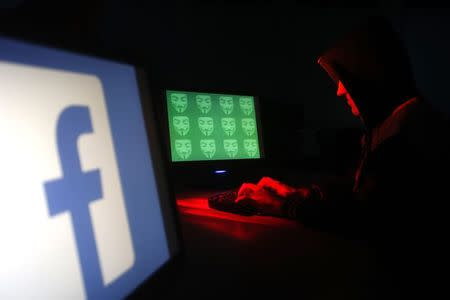 Man poses in front of on a display showing  a Facebook logo and the word 'cyber' in binary code, in this picture illustration taken in Zenica December 27, 2014.  REUTERS/Dado Ruvic/Files