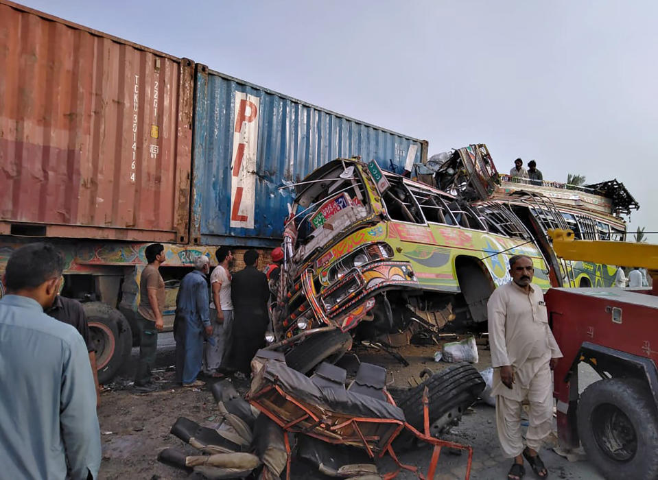 In this handout photo released by Punjab Province's Emergency Service Rescue 11222, shows residents and rescue workers at the site of a deadly bus accident near Dera Ghazi Khan, Pakistan, Monday, July 19, 2021. The speeding bus carrying mostly laborers traveling home for a major Muslim holiday rammed into a container truck on a busy highway in central Pakistan, killing and injuring dozens, police and rescue officials said. (Emergency Service Rescue 1122 via AP)