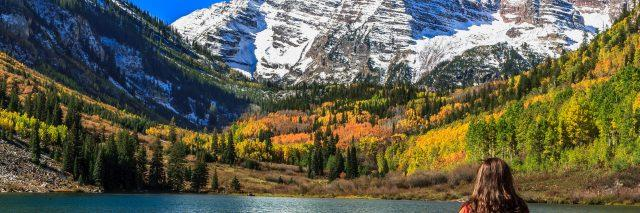 A woman admiring the autumnal beauty of the snowcapped Maroon Bells and the colorful foliage of the aspen groves on a sunny, cloudless day.