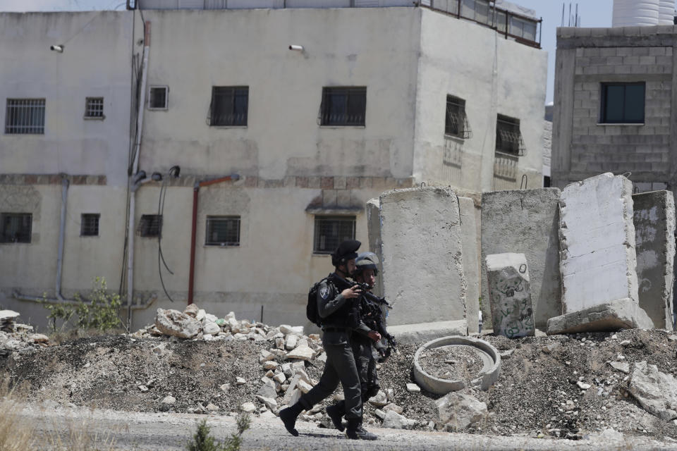Israeli police work at the site of a vehicle attack near Hizmeh Junction in the West Bank, Wednesday, June 16, 2021. The Israeli military on Wednesday shot and killed a Palestinian woman who it said tried to ram her car into a group of soldiers guarding a West Bank construction site. (AP Photo/Maya Alleruzzo)