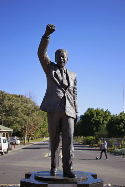 A boy kicks a ball behind a statue of former South African President Nelson Mandela outside the Groot Drakenstein correctional facility near the town of Franschhoek, South Africa, Sunday, June 9, 2013. Former South African President Nelson Mandela was receiving medical treatment for a lung infection on Sunday after spending a second night in a hospital. (AP Photo/Schalk van Zuydam)