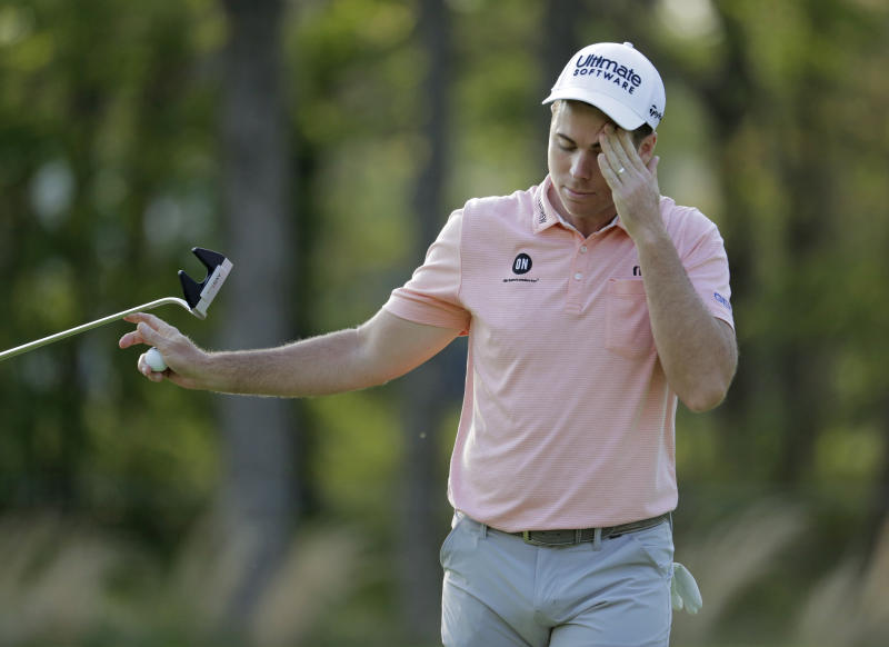 Luke list hands his putter to his caddie after putting on the seventh green during the second round of the PGA Championship golf tournament, Friday, May 17, 2019, at Bethpage Black in Farmingdale, N.Y. (AP Photo/Julio Cortez)