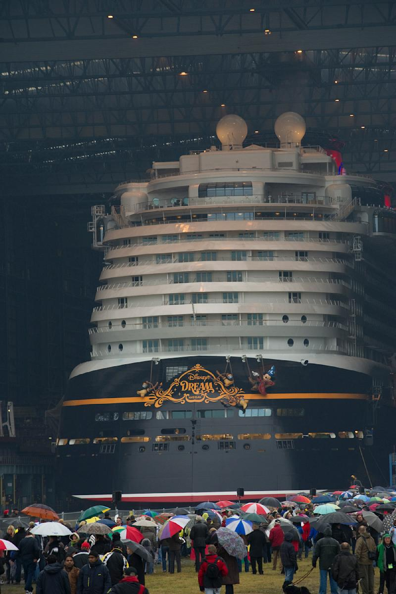 """This image provided by the Disney Company shows the Disney Dream cruise ship, the largest built in Germany,  making its first public appearance Saturday Oct. 30, 2010 in Papenburg, Germany as it begins to exit an enclosed building dock, pulled by a tugboat.  Thousands of local residents gathered to see the """"float out"""" ceremony.  The new ship is scheduled to sail its maiden voyage Jan. 26, 2011 from Port Canaveral, Fla. (AP Photo/Diana Zalucky- Disney)"""