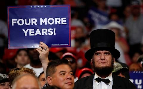 A supporter holds a placard during a campaign rally for U.S. President Donald Trump formally kicking off his re-election bid in Orlando - Credit: Reuters