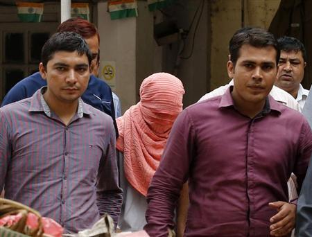 Plainclothes policemen escort a teenager (head covered with towel) after he was sentenced at a juvenile court in New Delhi August 31, 2013. REUTERS/Anindito Mukherjee