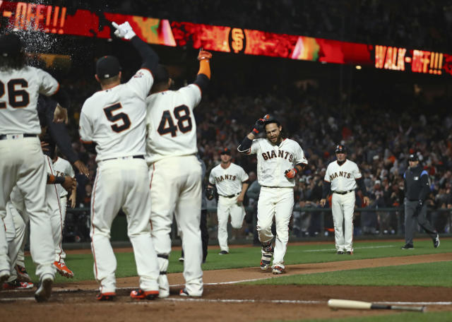 San Francisco Giants' Brandon Crawford, second from right, removes his helmet as he nears home after hitting a walk-off home run off Colorado Rockies Harrison Musgrave during a baseball game Wednesday, June 27, 2018, in San Francisco. The Giants won 1-0. (AP Photo/Ben Margot)