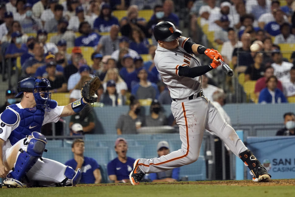San Francisco Giants' Wilmer Flores connects for a two-run home run during the ninth inning of the team's baseball game against the Los Angeles Dodgers on Wednesday, July 21, 2021, in Los Angeles. (AP Photo/Marcio Jose Sanchez)
