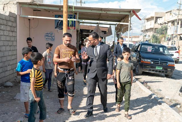 Qusay Abdullah, in suit, speaks with potential voters as he walks on his street in the poor neighborhood of Tel Roman in Mosul. (Photo: Shawn Carrié for Yahoo News)