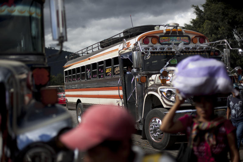 In this Nov. 14, 2013 photo, passengers walk after getting off a bus at the bus terminal in Antigua Guatemala. Bus drivers have been up in arms after one colleague was killed and another wounded in separate attacks because they refused to pay extortion money. The drivers only fully re-established service after the government pledged to crack down on the extortions. (AP Photo/Luis Soto)