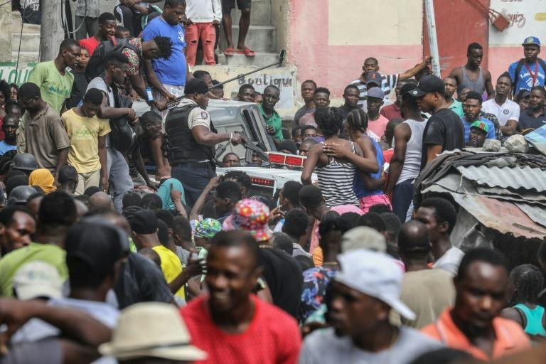 Crowds watch as two men, accused of being involved in the assassination of President Jovenel Moise, are transported to the Petionville station in a police car in Port-au-Prince